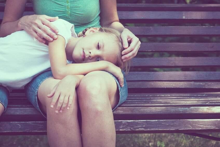 En pige hviler hovedet på sin mors skød