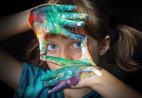 Pige med maling på hænderne danner firkant med fingre foran øjne