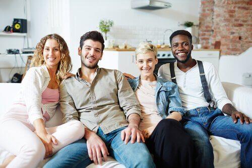 To mænd og to kvinder smiler på sofa