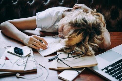 Træt kvinde ligger hen over skrivebord