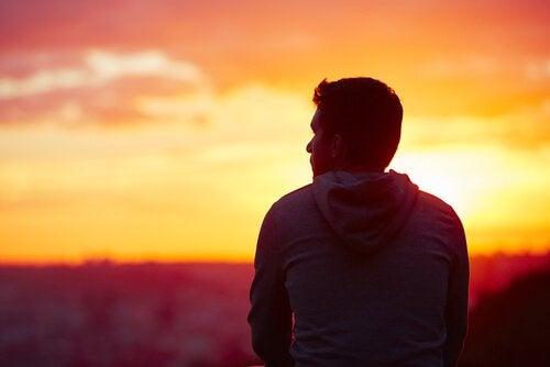 Mand ser ud over solnedgang