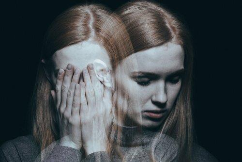 Kvinde skjuler ansigt i hænder for at udtrykke traumer