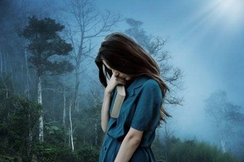 En trist pige i skov, der frygter at blive forladt