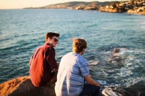 Venner sidder ved vandet og taler