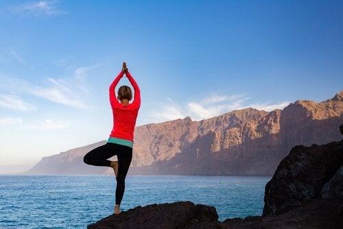 Kvinde laver yogaøvelser ved bjerge og sø