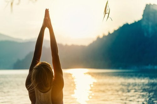 Kvinde laver yogaøvelser ved sø