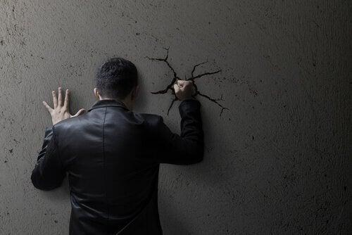 En arrig mand slå revner i muren