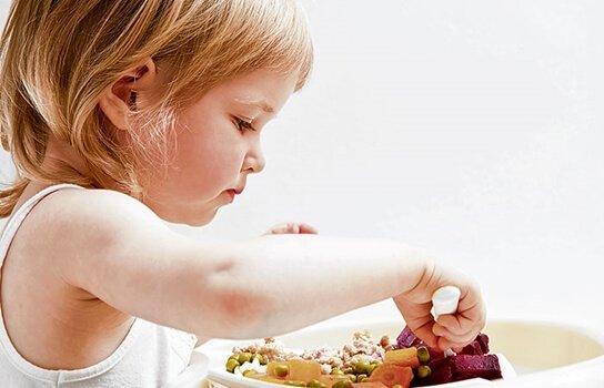 Pige spiser med hænderne