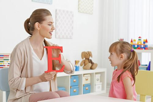 Pige øver sig på at læse bogstaver