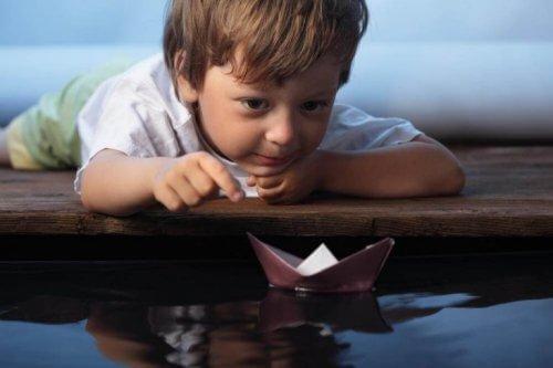 Dreng leger med papirsbåd