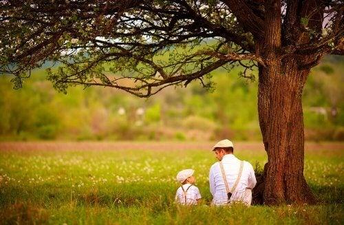 Far og søn taler sammen under træ
