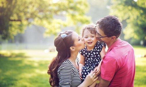 Forældre kysser datter på kinderne