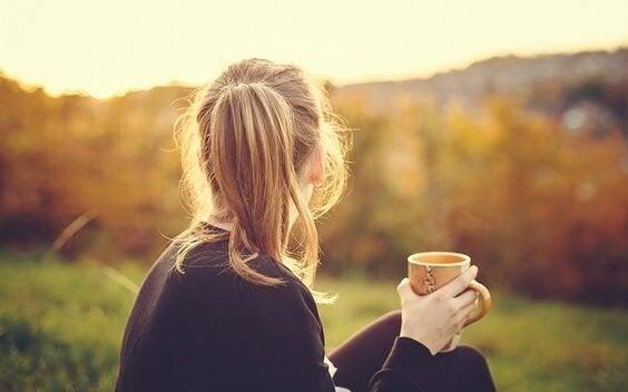 Kvinde drikker varm te ved skov