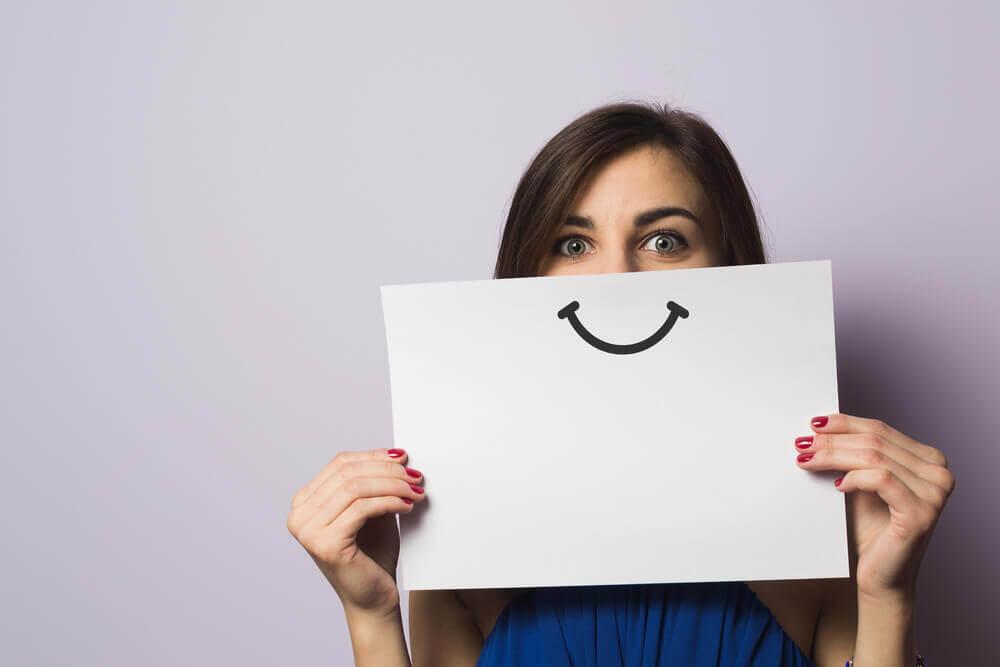 Kvinde med papir med smil foran mund