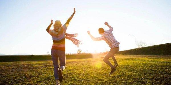 Personer danser i solen på eng