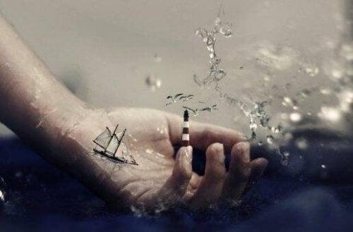 En hånd i vand, med en lille båd og et fyrtårn på fingeren