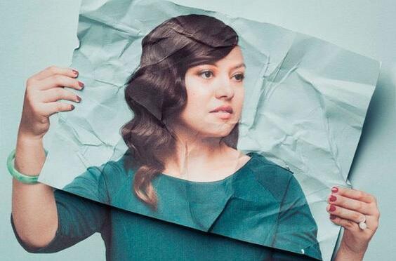 Kvinde med krøllet billede af sig selv foran ansigtet