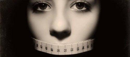 Kvinde med målebånd om munden