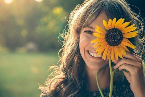 Smilende kvinde med solsikke foran øje