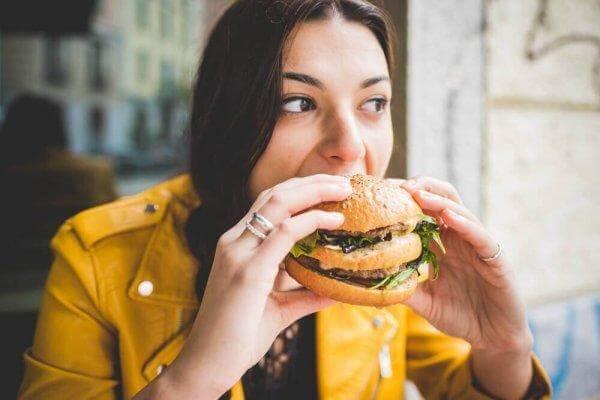 Kvinde spiser stor burger