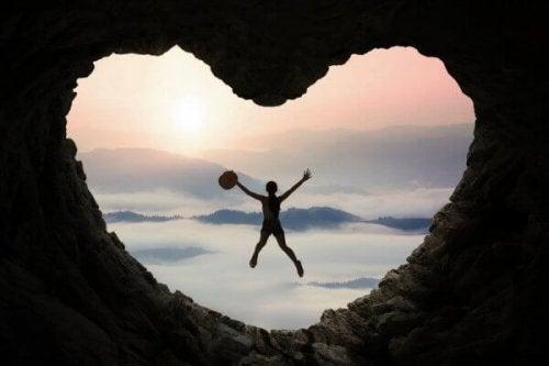 En kvinde springer frem fra en hjertformet grotte
