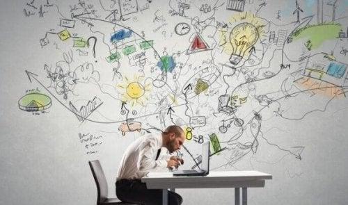 Fokuseret mand ved computer har masser af ideer, der ses som tegninger