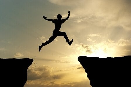 Mand med balanceret motivation hoppe mellem to klipper