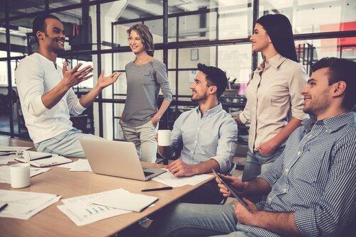 Smilende personer på kontor illustrerer et godt arbejdsmiljø