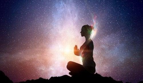 En kvinde mediterer under en stjernehimmel