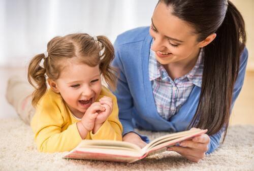 Mor og datter griner over bog, da det skal være sjovt for barnet at lære at læse