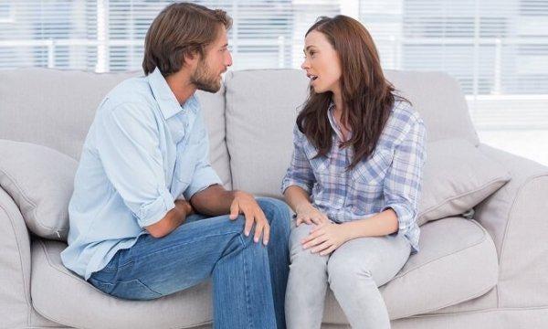 Par på sofa diskuterer
