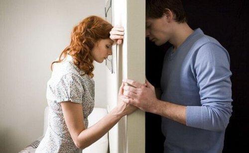 Mand og kvinde på hver sin side af væg holder stadig i hånd
