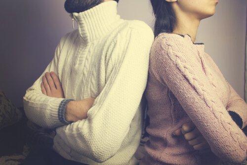 Par sidder med ryg mod hinanden og foldede arme som resultat af en krise i ægteskabet