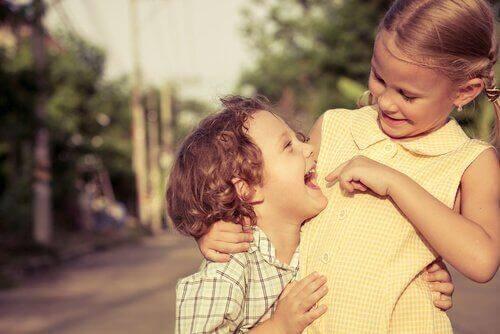 To søskende krammer og smiler sammen