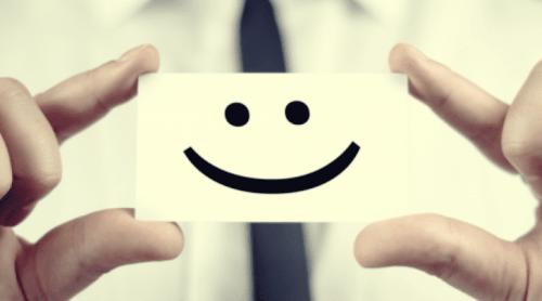 Smiley på papir holdes af fire fingre
