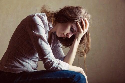 Kvinde i dybe tanker tager sig til hoved
