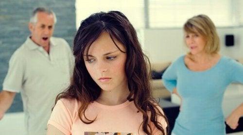 Forældre diskuterer bag fortvivlet teenagepige