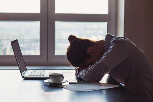 Kvinde hviler hoved på bord, da hun har svært at vende tilbage til hverdagen