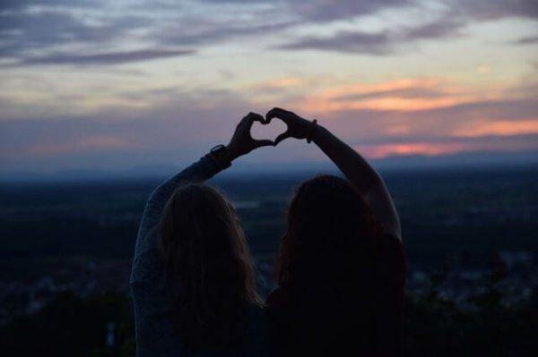 To personer danner hjerter med hænderne