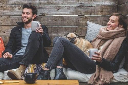 To venner griner og drikker kaffe udenfor med hund