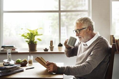 Ældre mand læser, mens han drikker kaffe