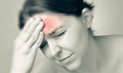 Kvinde med smerte i panden illustrerer migræne