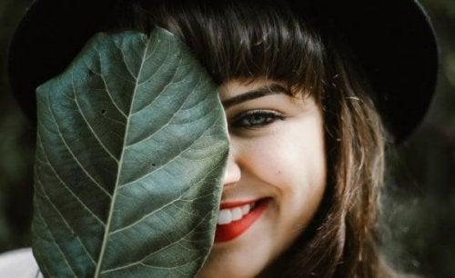 Smilende kvinde gemmer det ene øje bag stort blad