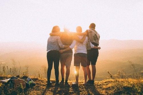 Venner står med armene om hinanden og nyder landskab