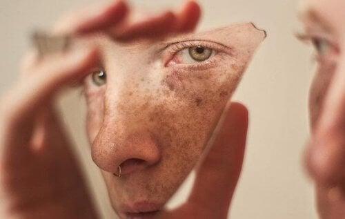 Person kigger på sig selv i stykke af spejl