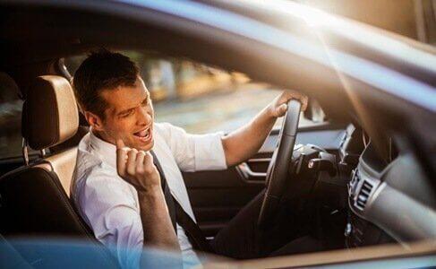 En mand synger i sin bil og viser, at faktisk gør sang os lykkeligere