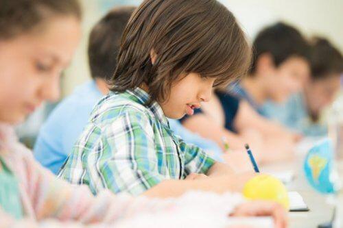 Dreng skriver med blyant