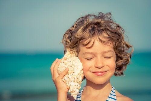 Pige lytter til konkylie på strand
