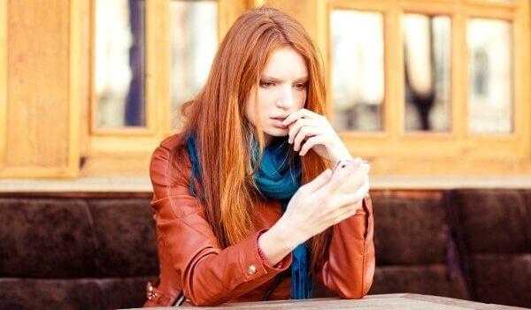 kvinde ser bekymret på sin telefon