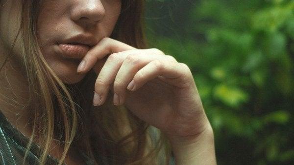 ung kvinde er bekymret og tager sig til mund